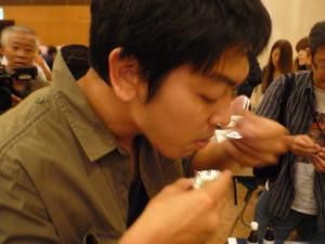 イナゴソースとふきとサバの煮物を試食する加藤室長